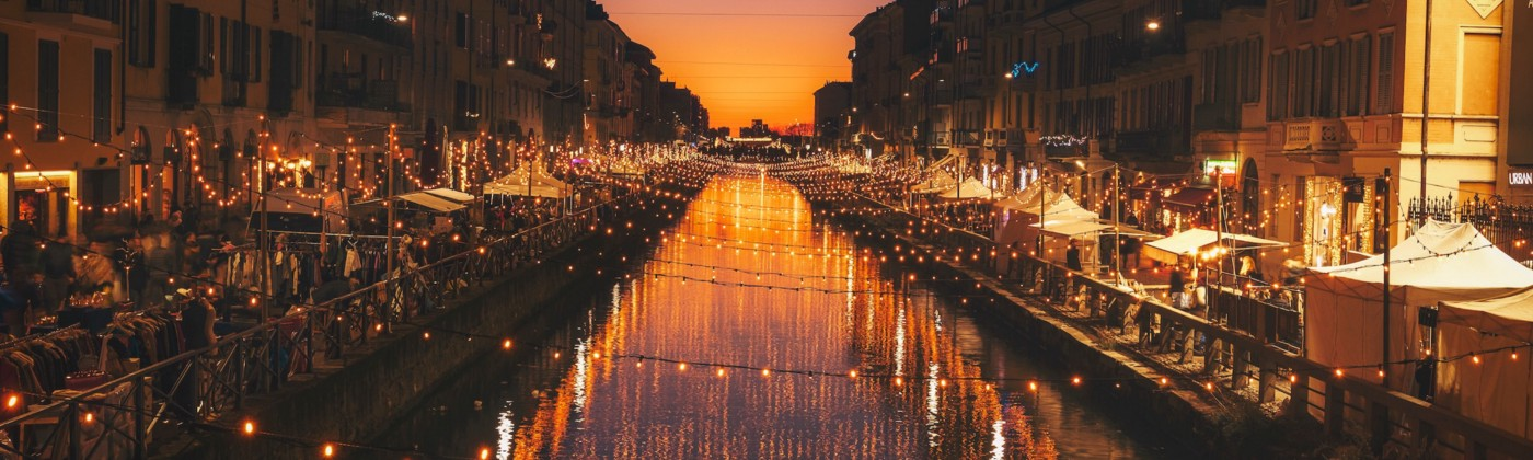 A canal at sunset, stretching to the horizon and lined with lights and shops.