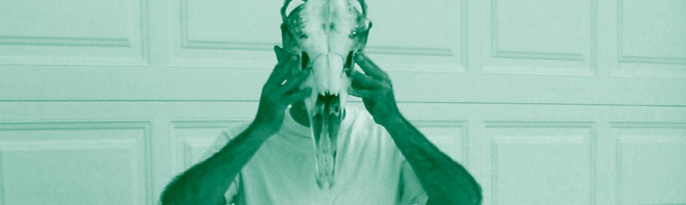 A teal-tinted photo of a person standing in front of a garage door, holding a large horse skull up in front of their face.