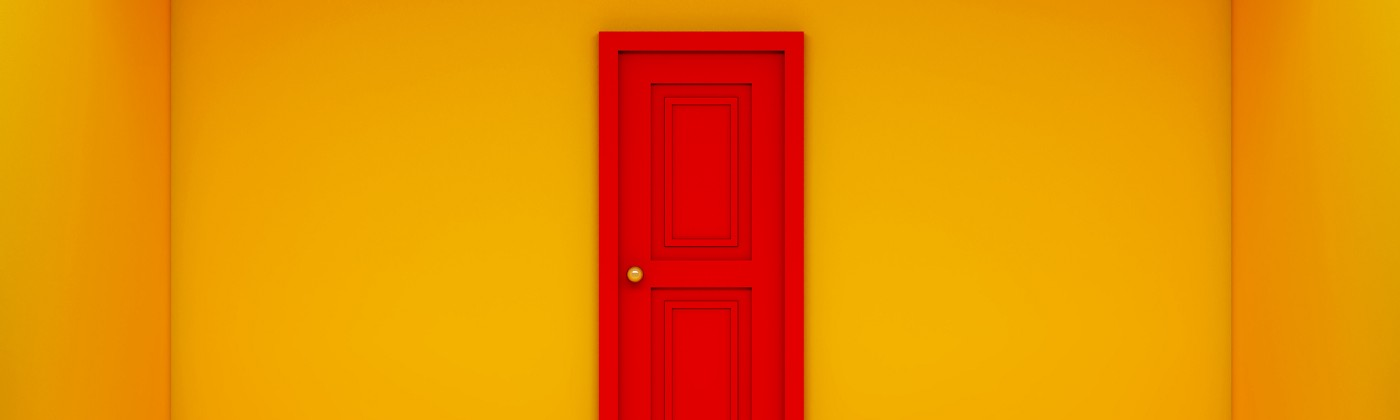 A photo of a red door in an empty room with bright yellow walls.