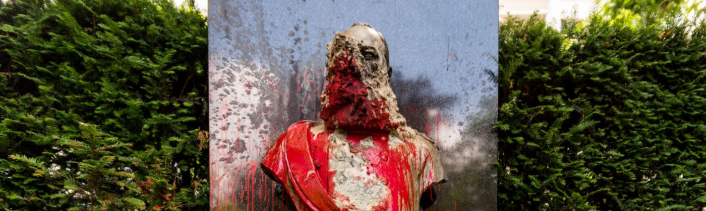 A photo of a vandalized statue of King Leopold II in Belgium. It is covered in red paint and graffiti.
