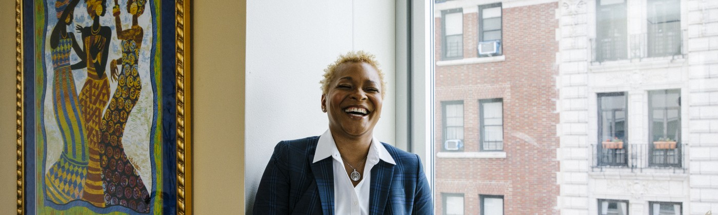 Rev. Dr. LaKeesha Walrond laughs while sitting on a window ledge in her fifth floor Upper Manhattan office.