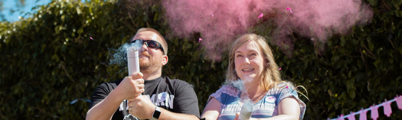 Two smiling adults, holding smoking tubes. A tiny bit of blue smoke comes out of one, and a lot of pink smoke from the other