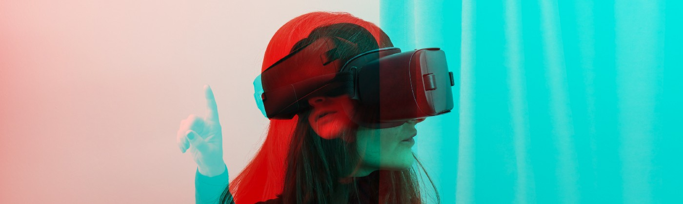 A double exposure photograph of a woman wearing VR Glasses in two different poses.