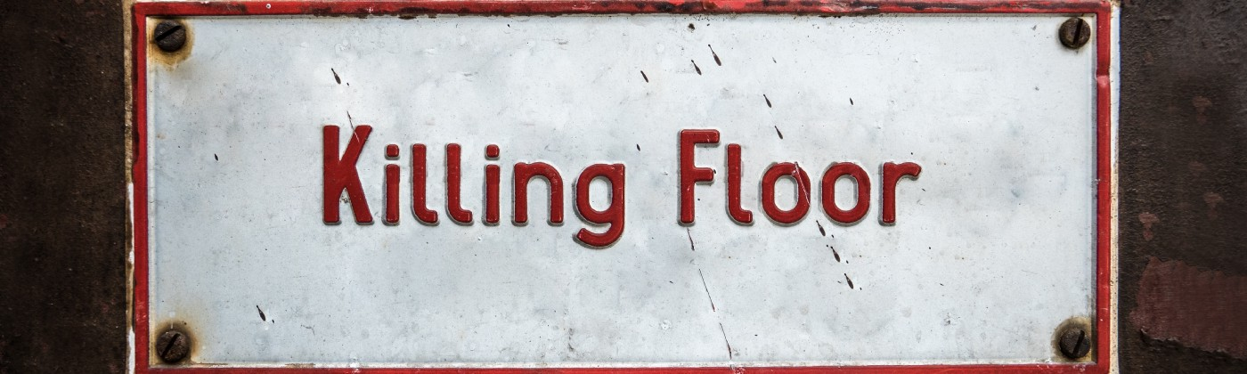 "A white metal sign that reads ""Killing Floor"" in red lettering."