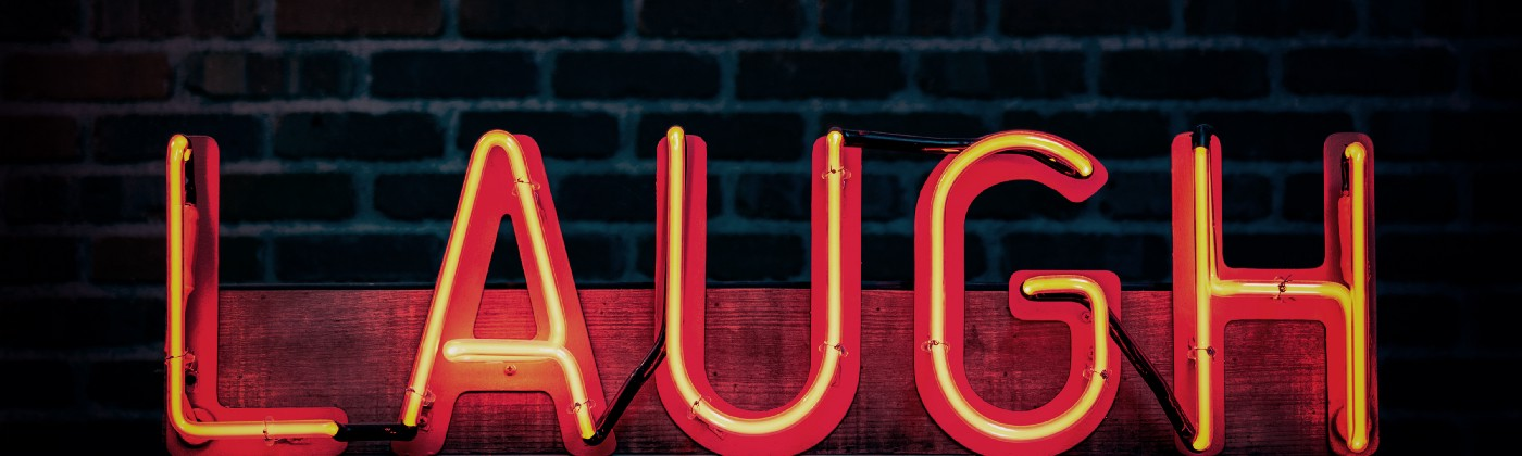 The word laugh has been created out of read and yellow neon lettering against a black brick wall