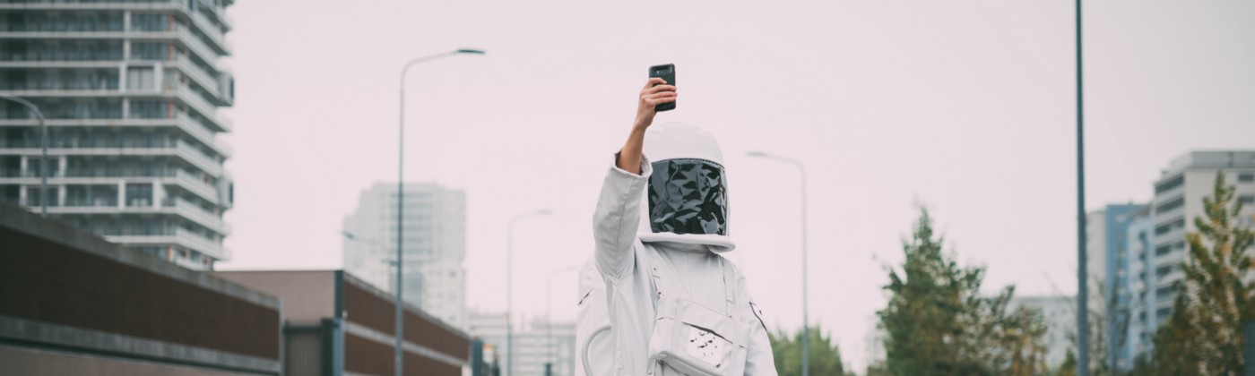 Person wearing astronaut standing in empty street with phone raised, taking a selfie.