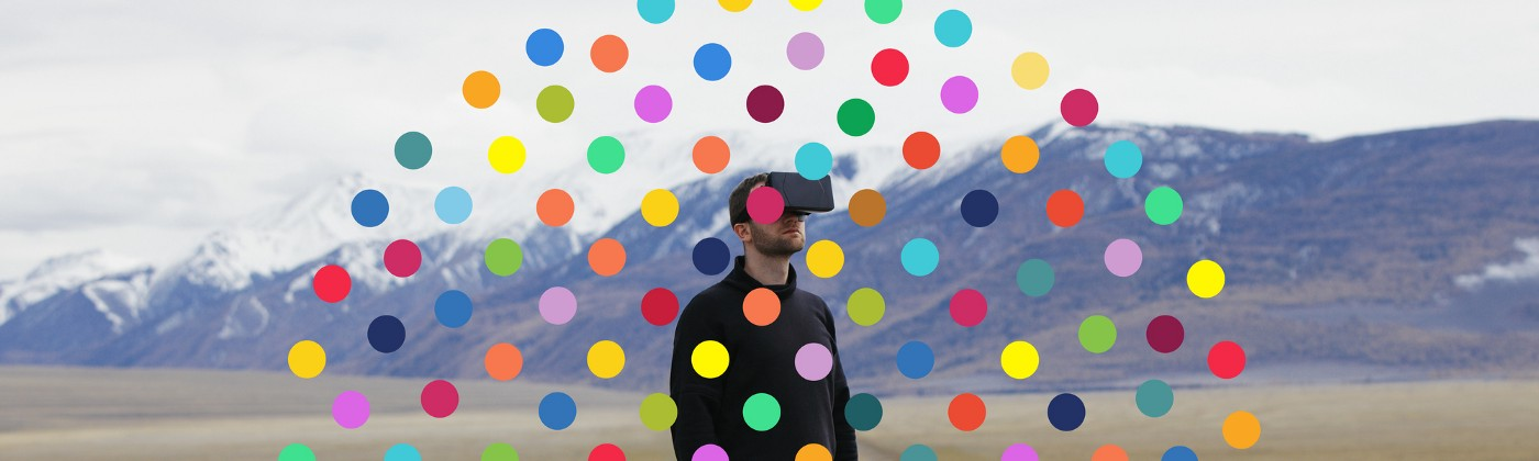 A man wearing a virtual reality headset against a nature background surrounded by a circle of colorful dots.