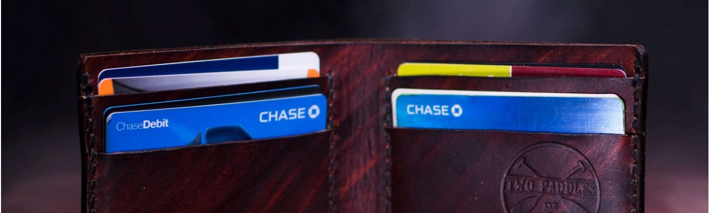 A bi-fold wallet open to show a bunch of credit cards.