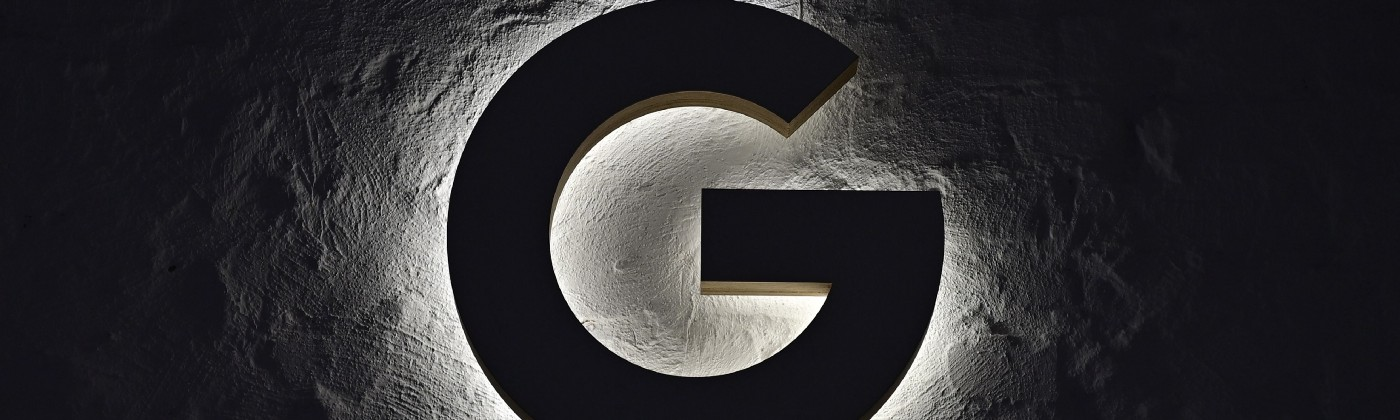 "An illuminated ""G"" hangs on the wall."