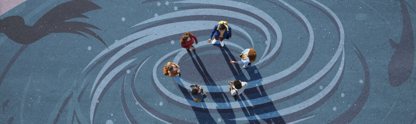 A group of young adults in a circle facing each other, photographed from above, on a painted tarmac surface showing a vortex.