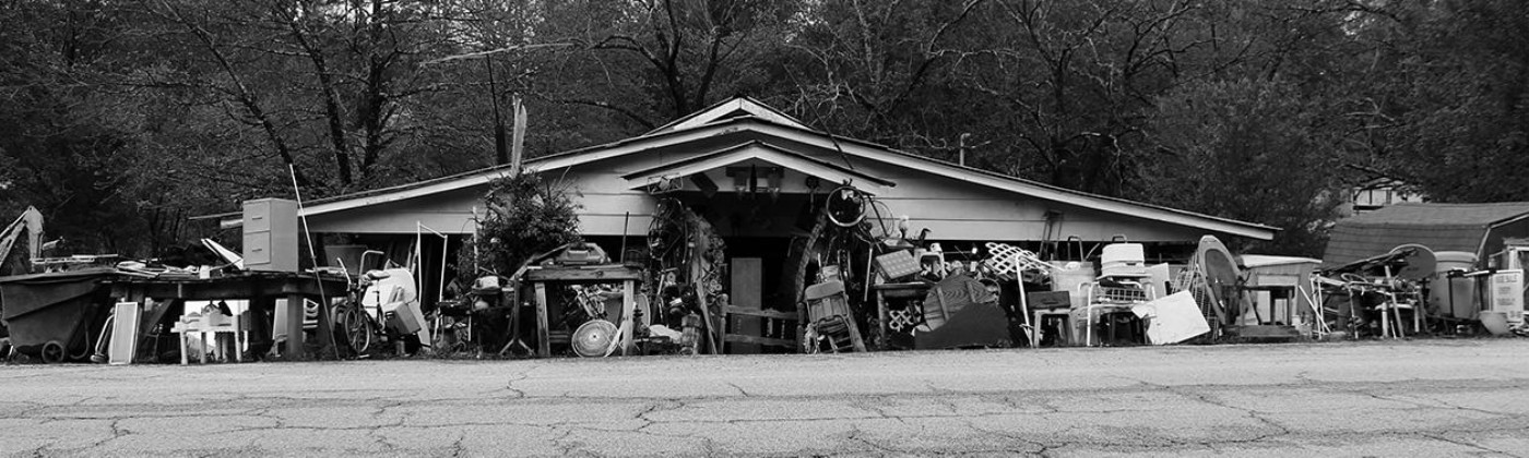 A black-and-white photo of the front of a run-down house with junk in the front yard.