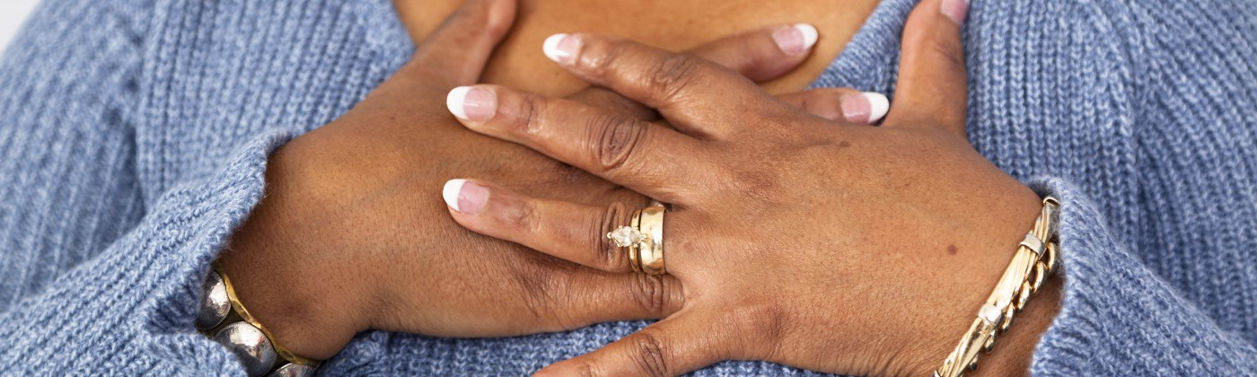 A close-up photo of a woman clasping her hands over her chest.
