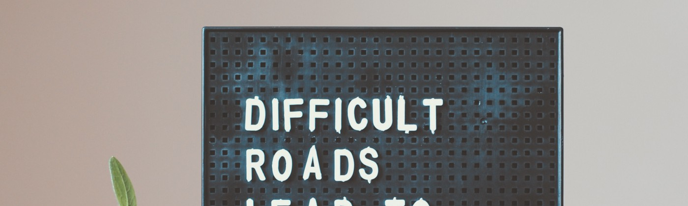 """Letter board and a plant. """"Difficult roads lead to beautiful destinations."""""""