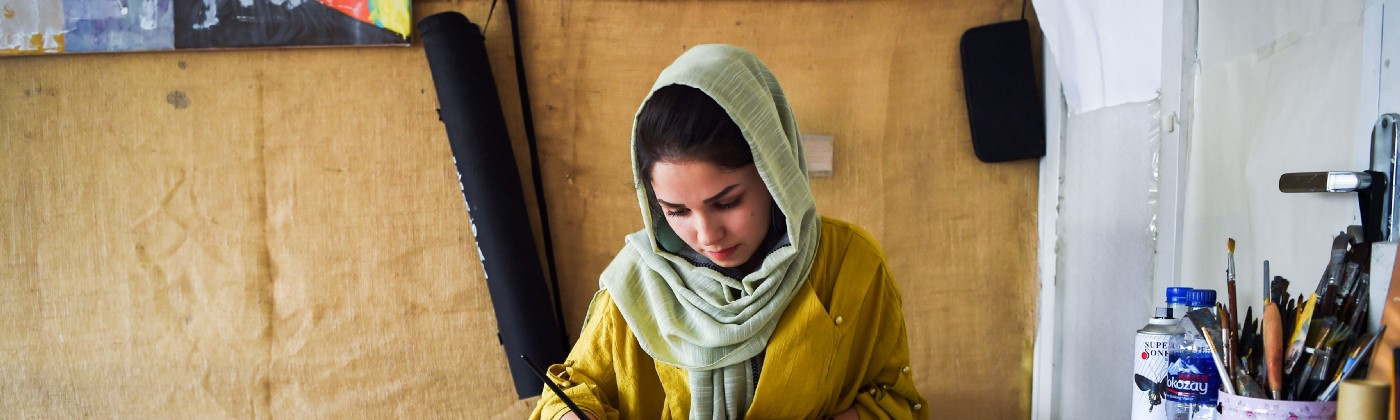 A 24-year-old artist and designer Zahra works in her office in Kabul.