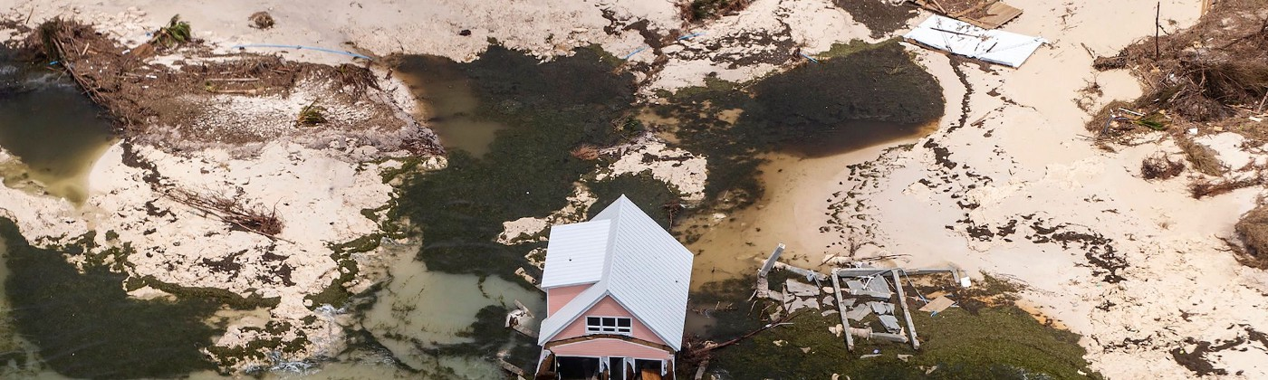 An aerial view of a single pink house flooded up to its porch with silty water.