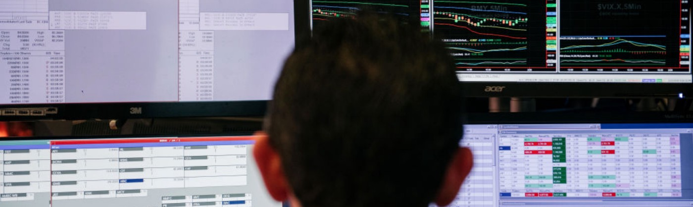 A photo that shows the back of a man's head as he looks at stocks on four computer screens.