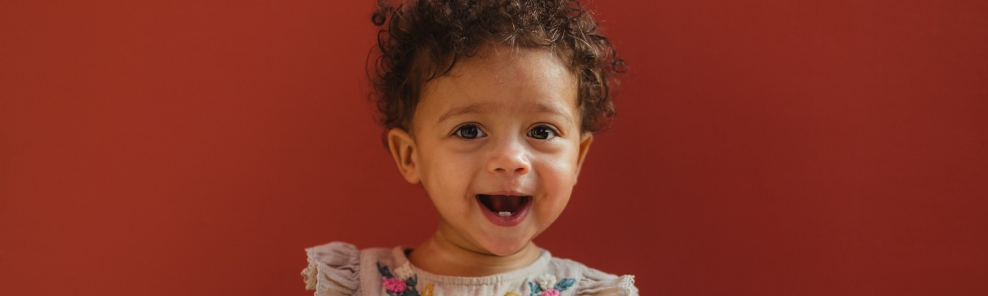 Adorable, curly-haired toddler with cute little teeth