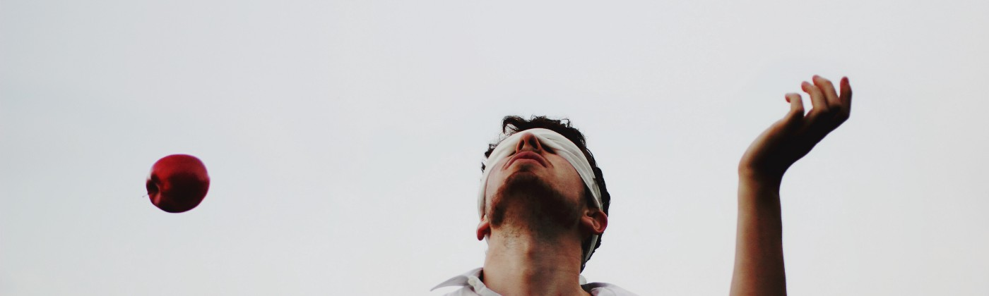 A man juggles 4 apples in the air while blindfolded.