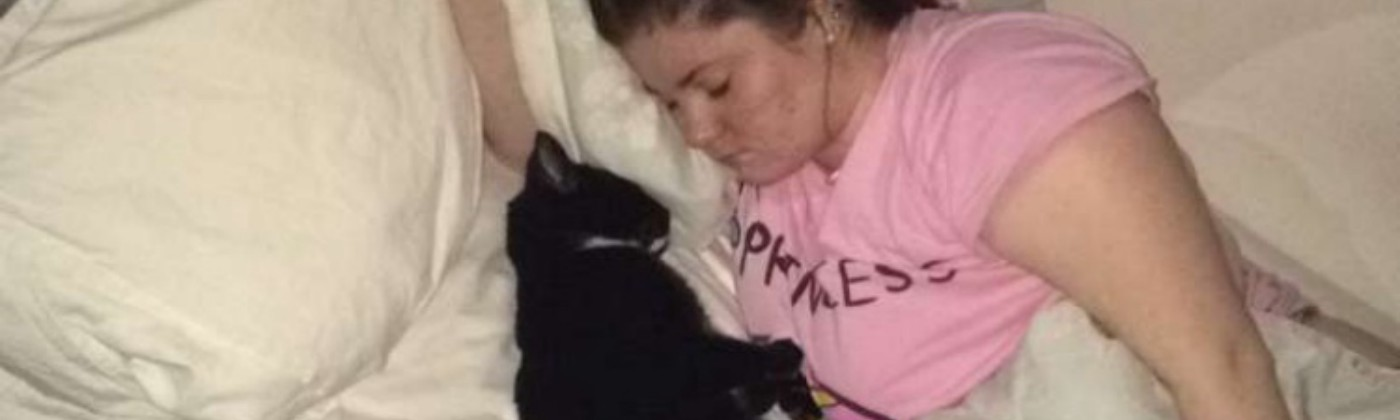 A photo of me lying in my bed asleep with my cat lying asleep very close to me facing me