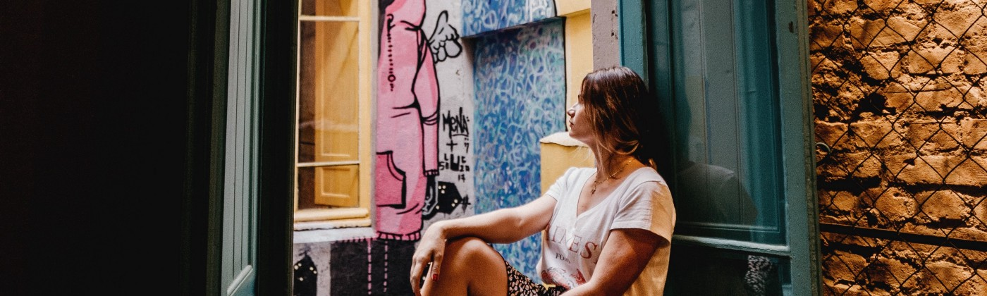 Barefoot woman sits on windowsill, gazing out open window onto a courtyard with street art