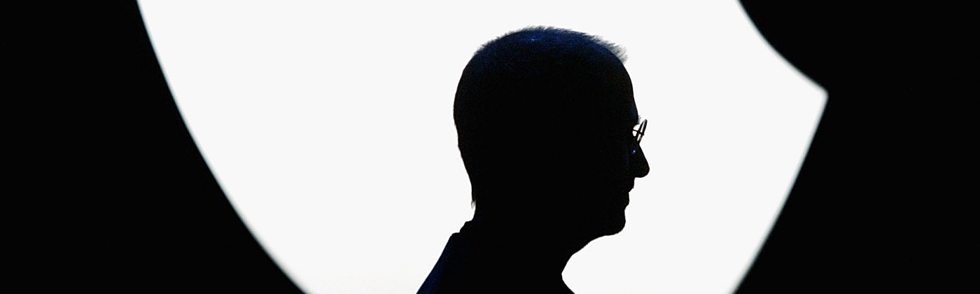 A silhouette of Steve Jobs' profile against the Apple logo during the 2004 Apple Worldwide Developers Conference keynote.