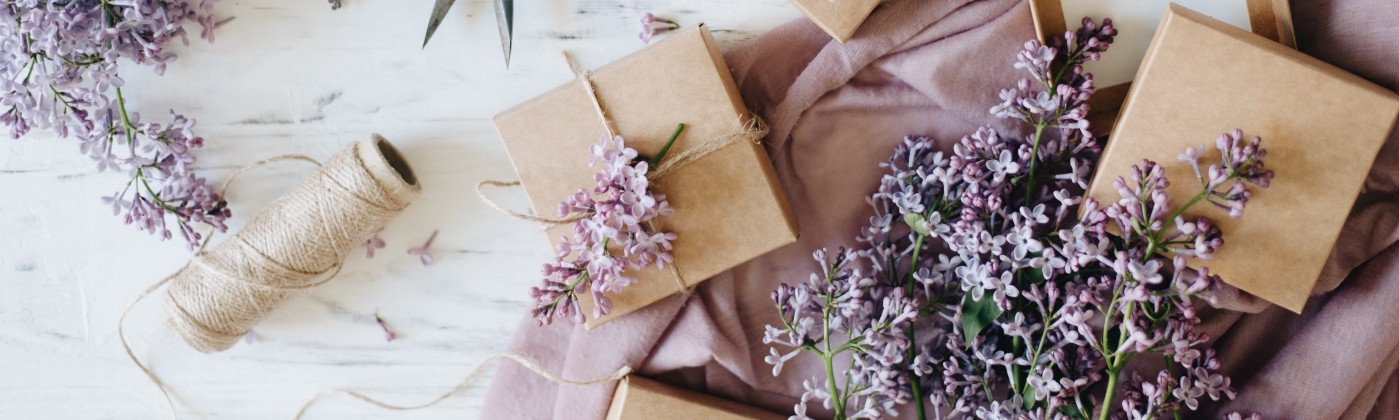 Rustic, yet fancy, gift wrapping supplies, including little brown boxes, twine, gardening shears, and fresh purple flowers