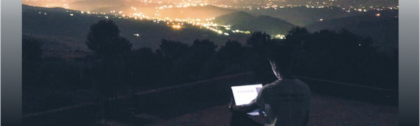 Young man working on laptop overlooking a city at night