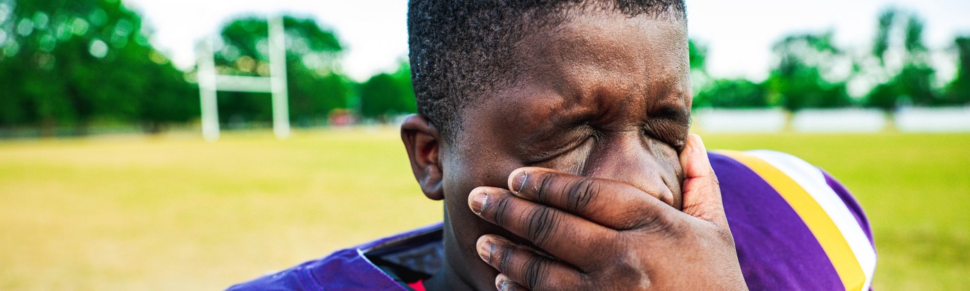 A close-up of a young football player rubbing his face with his hand in exhaustion.