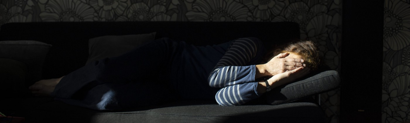 A woman lying sideways on a sofa covering her face with her hands.