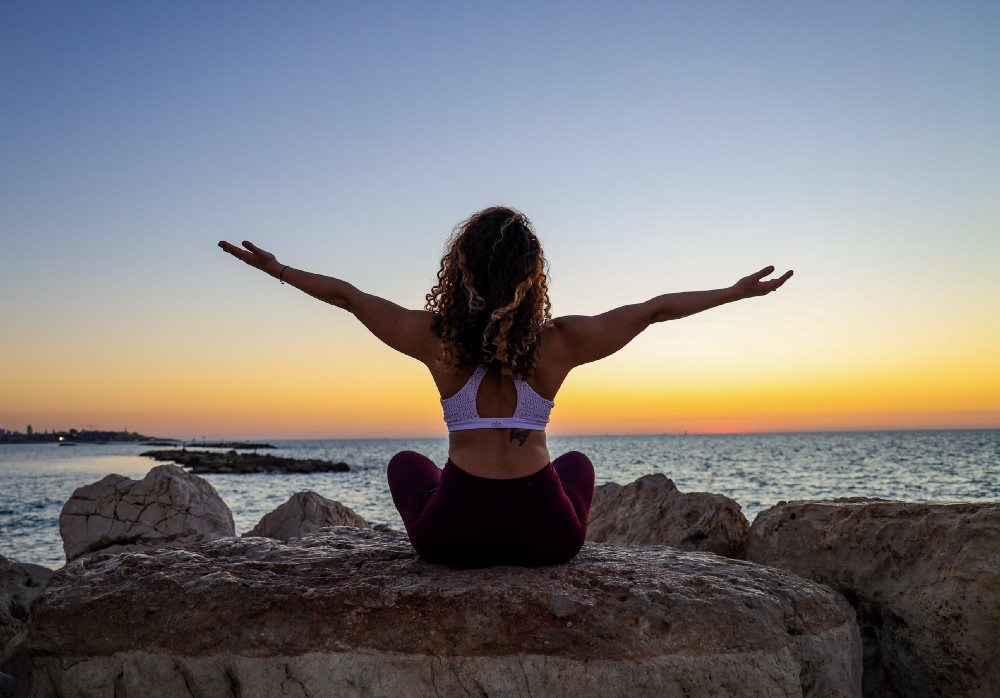 Woman doing yoga in front of the sea and sunset