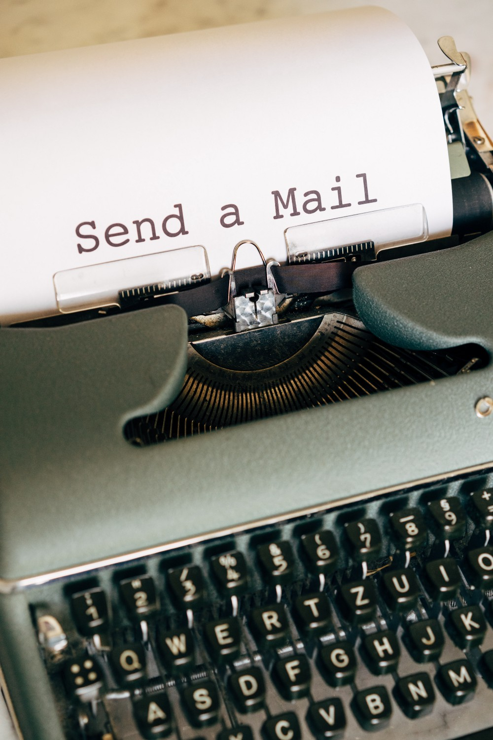 Typewriter with a paper with words typed: Send a Mail