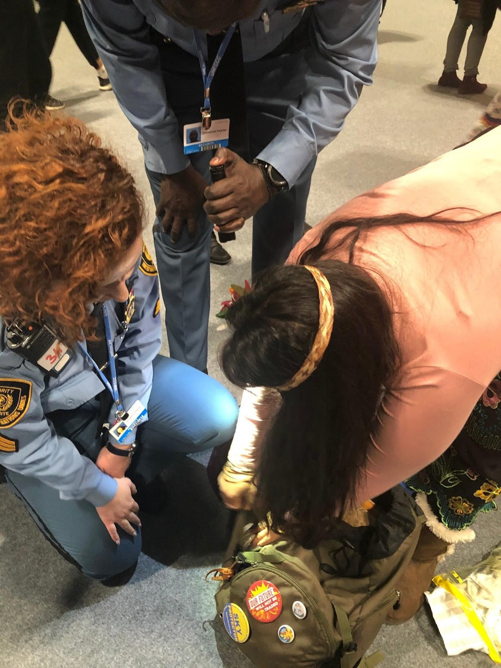 Activist Moneka de Oro opening her backback for two police officers at COP25.