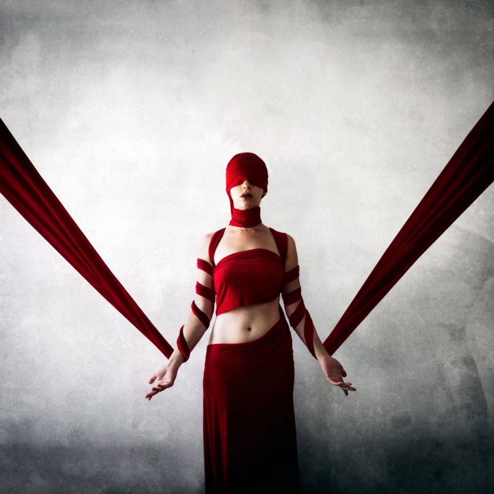 A woman in a red hood stands wrapped in red bandages and a red skirt. Image copyright Jen Kiaba.