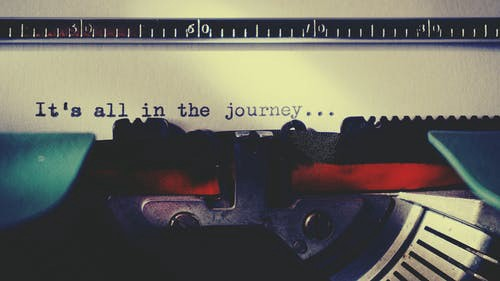 a typewriter with the words it's all in the journey written in black ink
