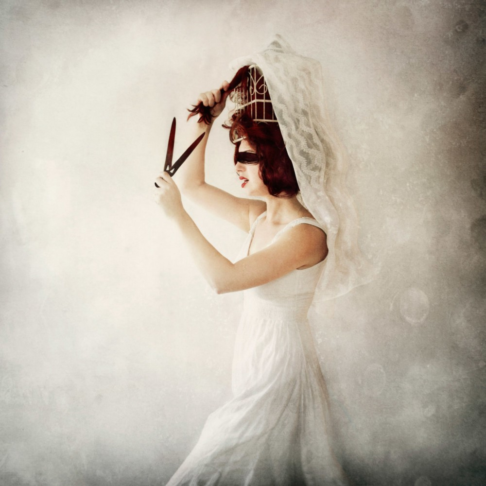 A red headed woman in a white dress with a blindfold pulls at her hair that is tangled in a bird cage while holding rusty scissors. Image copyright Jen Kiaba.