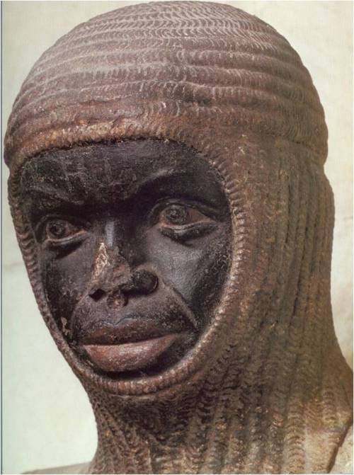 A close-up image of the statue shows the head of a Black man in a chainmail coif.