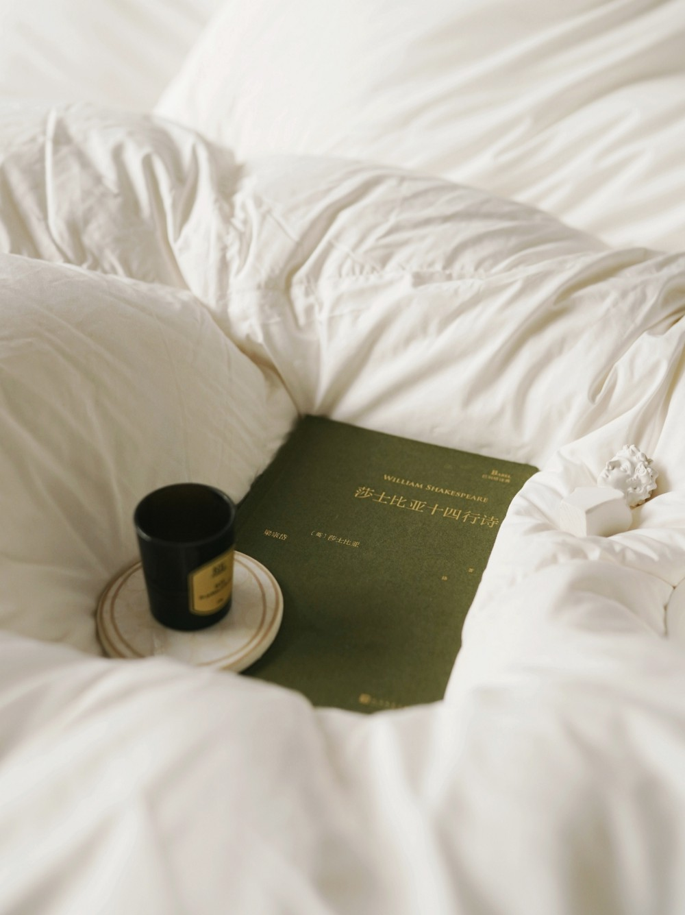 An olive green book of Shakespeare nestled in a white duvet with a cup and saucer