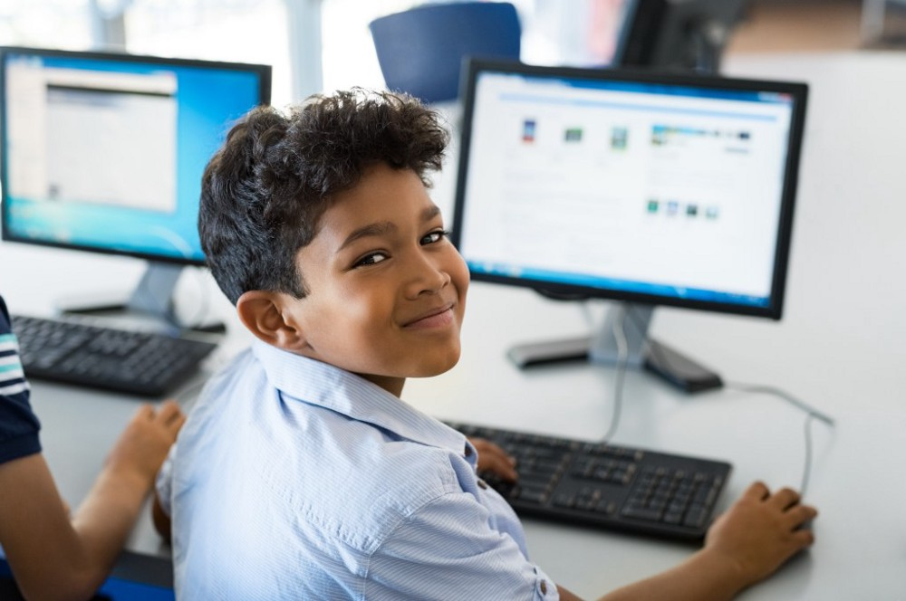 Little kid studying on computer in classroom in India