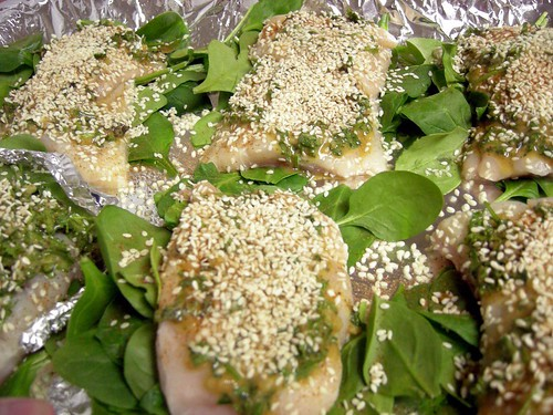 Uncooked catfish fillets covered with herbs, spices, and sesame seeds on beds of spinach leaves on a foil covered baking sheet.