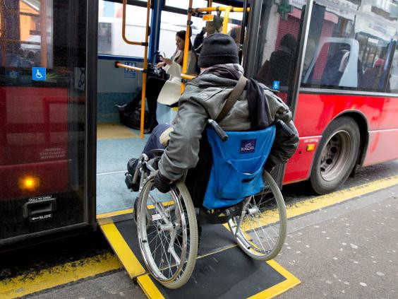Man in wheelchair using a ramp to access a London bus