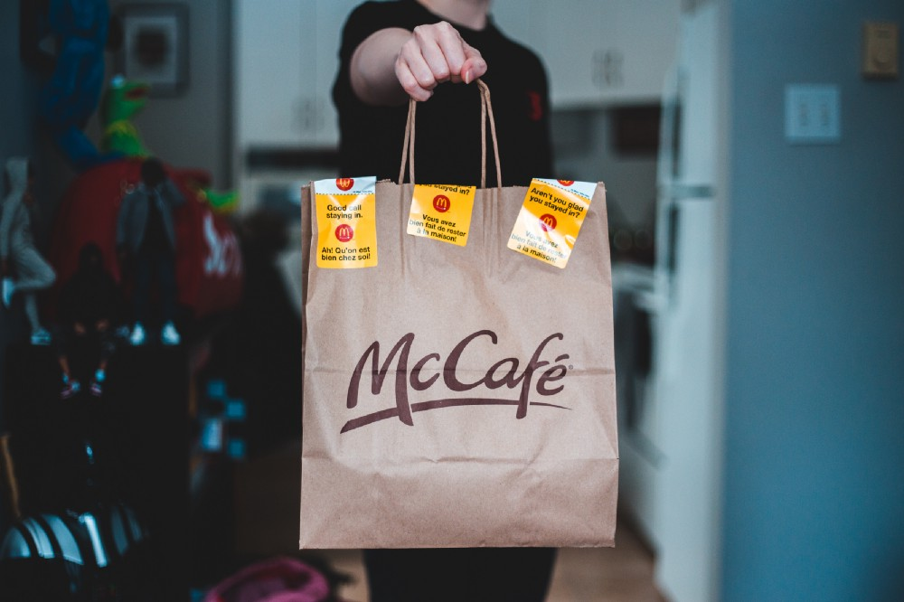Crew member holding out takeout bag
