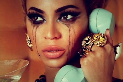 A still of Beyoncé, mascara running down her cheeks as if she's been crying. She's holding a light blue handset to her ear