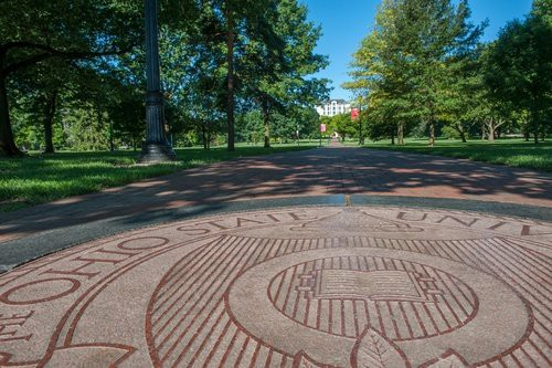 A view of the Ohio State Oval, with the university seal in the foreground. In the distance, the top of Thompson Library.
