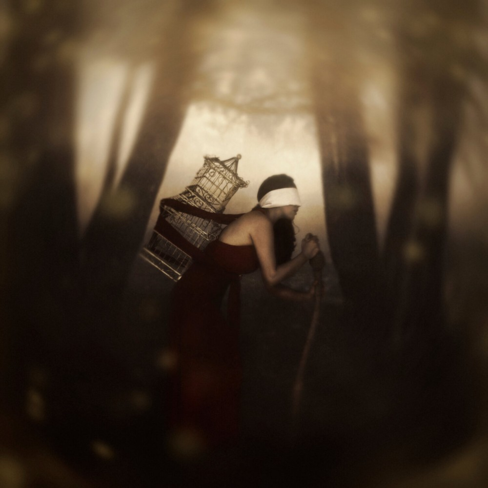 A woman in a white blindfold and red dress has a birdcage tied to her back as she hikes through a misty forest while leaning on a walking stick. Image copyright Jen Kiaba.