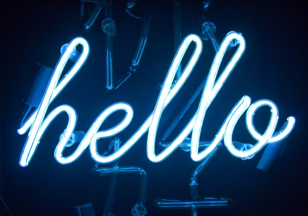 """""""Hello"""" written in bright blue cursive lights with black background."""