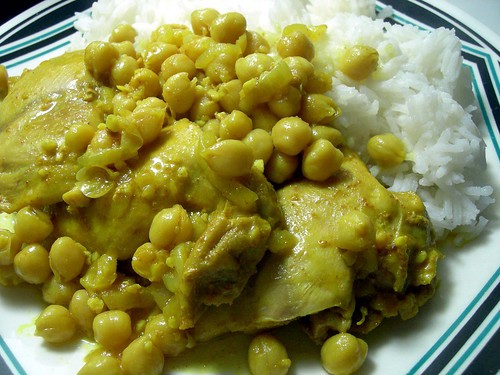 Cooked chicken thighs with chickepeas and white rice on a plate.