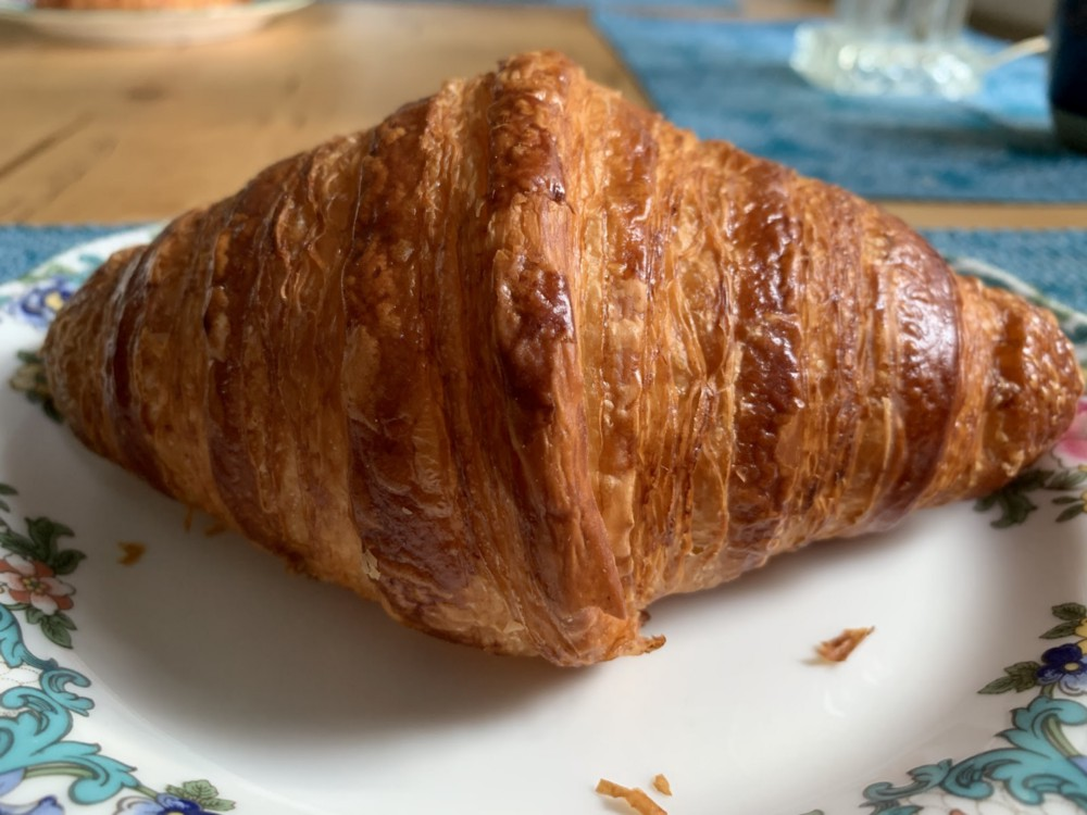 A golden brown crispy croissant on a china plate