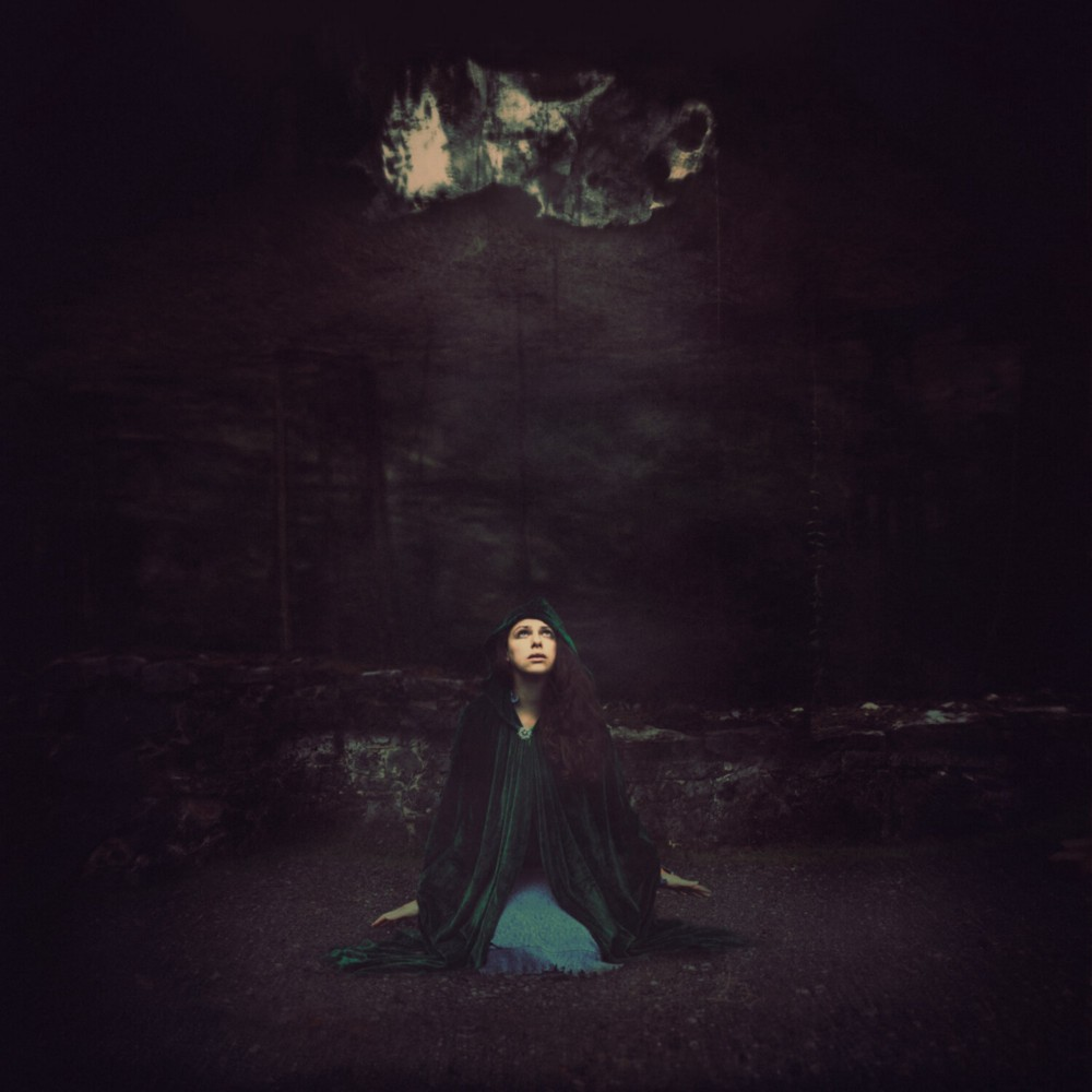 A woman in a green cloak kneels in a cave looking up at light coming in through a crack. Image copyright Jen Kiaba.