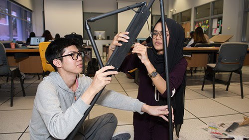A man wearing glasses and a woman wearing glasses and a headscarf work together to build a prototype with black pipes.