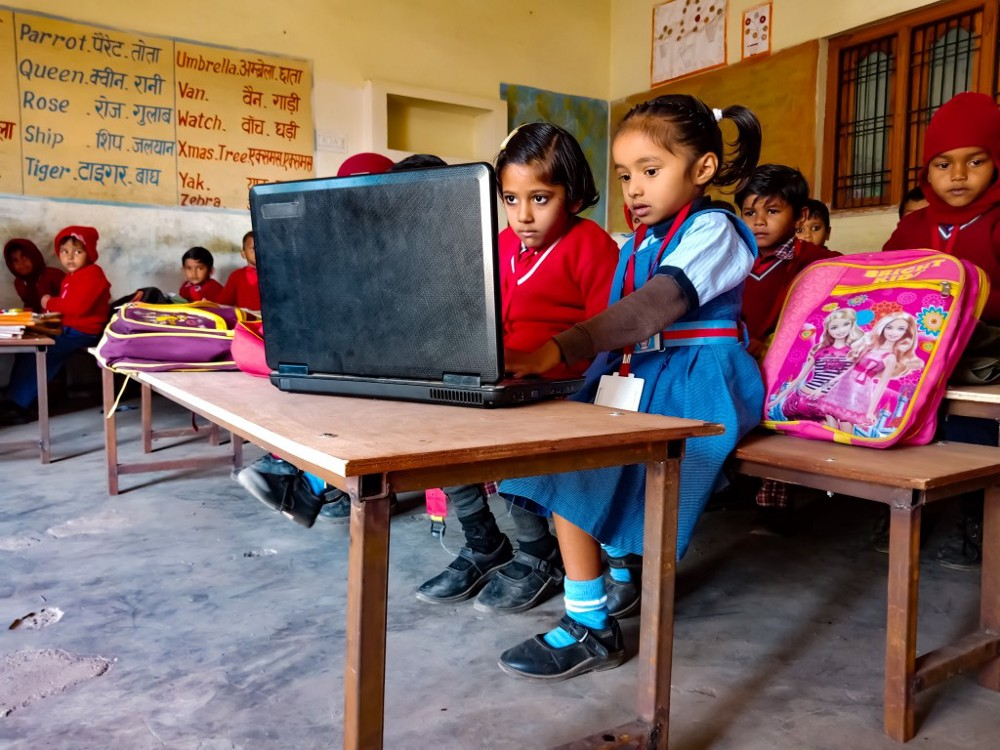 Little girls studying on laptop in classroom in India